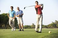 Stock Photo of Group Of Male Golfers Teeing Off On Golf Course