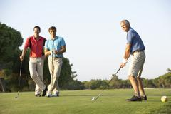 Group Of Male Golfers Teeing Off On Golf Course Stock Photos