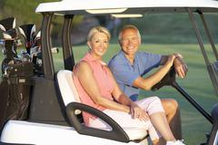 Senior Couple Riding In Golf Buggy On Golf Course - stock photo