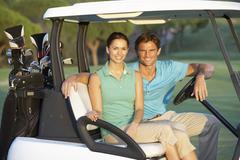 Couple Riding In Golf Buggy On Golf Course - stock photo