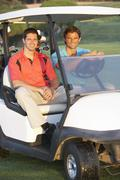 Two Male Golfers Riding In Golf Buggy On Golf Course Stock Photos