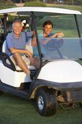Two Male Golfers Riding In Golf Buggy On Golf Course - stock photo