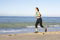 Young Woman In Fitness Clothing Running Along Beach Stock Photos