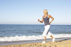 Senior Woman In Fitness Clothing Running Along Beach Stock Photos