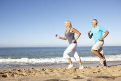 Stock Photo of Senior Couple In Fitness Clothing Running Along Beach