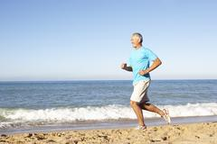 Senior Man In Fitness Clothing Running Along Beach Stock Photos