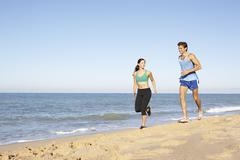 Young Couple In Fitness Clothing Running Along Beach Stock Photos