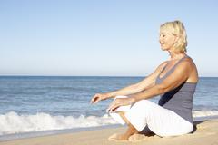 Senior Woman In Fitness Clothing Meditating On Beach Stock Photos