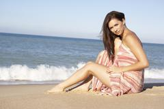 Stock Photo of Young Woman Relaxing On Beach Wearing Wrap