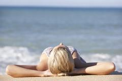 Young Woman Sunbathing On Beach Stock Photos