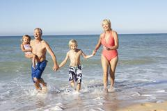 Grandparents With Grandchildren Enjoying Beach Holiday Together Stock Photos