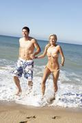 Young Couple Enjoying Beach Holiday - stock photo