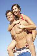 Young Couple Enjoying Piggyback On Beach Holiday - stock photo