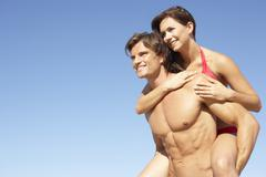 Young Couple Enjoying Piggyback On Beach Holiday Stock Photos