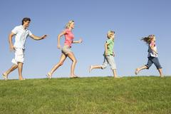 Young family, parents with children,  running through field Stock Photos