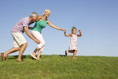 Senior couple, with granddaughter,  running though field Stock Photos