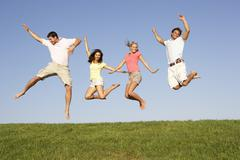 Young couples jumping in air - stock photo