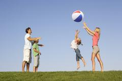Young family, parents with children,  playing in a field - stock photo