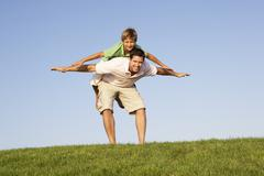 Young man with boy  playing in a field - stock photo