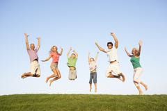 Young couple with grandparents and children jump in a field - stock photo