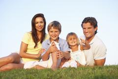 Young parents, with children, posing on a field - stock photo