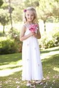 Portrait Of Bridesmaid Holding Bouquet Outdoors - stock photo