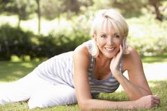Middle age woman posing in park - stock photo