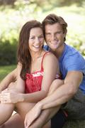Portrait Of Young Couple Relaxing In Park Stock Photos