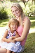 Portrait Of Mother And Child Relaxing In Park Stock Photos