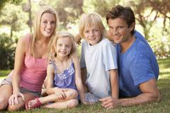 Young parents with children posing in a park Stock Photos