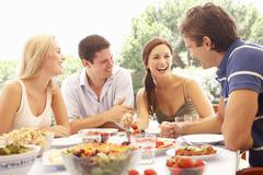 Two young couples eating outdoors Stock Photos