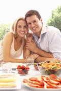 Young couple eating outdoors Stock Photos