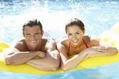 Young couple having fun in pool - stock photo