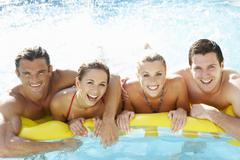 Group of Young friends having fun in pool Stock Photos