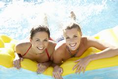 Two women friends having fun together in pool Stock Photos