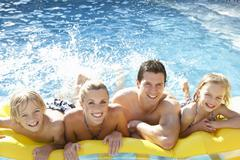 Young family having fun together in pool - stock photo