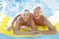 Senior couple having fun in pool Stock Photos