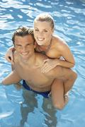 Young couple having fun in pool Stock Photos