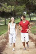 Young couple running in park Stock Photos
