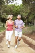 Senior couple running in park - stock photo
