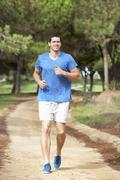 Young man running in park Stock Photos