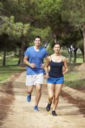 Couple running in park - stock photo