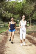 Two young women running in park - stock photo