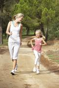 Mother and daughter running in park - stock photo