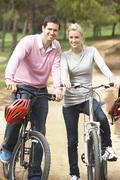 Couple riding bicycle in park Stock Photos