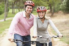 Couple riding bicycle in park - stock photo