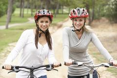 Stock Photo of Two Female friends riding bikes in park