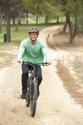 Man riding bicycle in park - stock photo