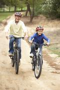 Grandfather and grandson riding bicycle in park - stock photo