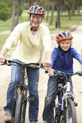 Grandfather and grandson riding bicycle in park Stock Photos